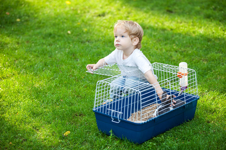 stroking: Cute boy stroking a pet rabbit in a cage outdoors