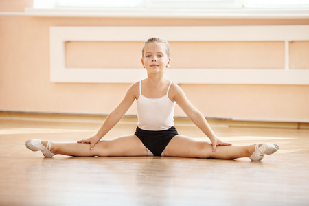 Young girl doing splits while warming up at ballet dance class Stock Photo