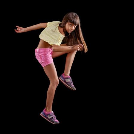 BLACK GIRL: Young girl dancing against black