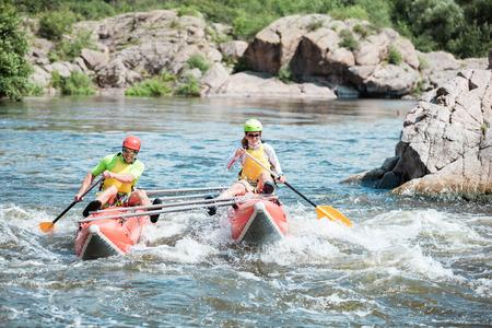Jong paar op een opblaasbare catamaran roeien de stroom