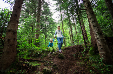Young woman and toddler son walking down a path in a mountainous forest