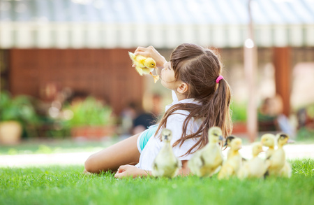 girl lying down: Cute girl lying down on grass and holding spring duckling