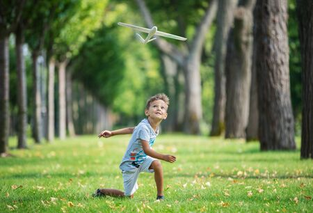 aeroplanes: Boy playing with toy glider in park on summer day