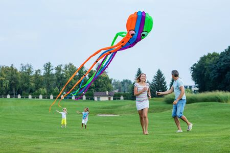 family life: Happy family flying kite together on a green field