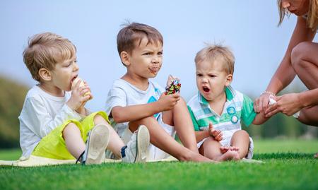 Dos chicos mayores que comen el helado, Barrido de la mujer joven manos del hijo menor Foto de archivo - 62366828