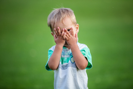peekaboo: Little boy playing peek-a-boo outdoors