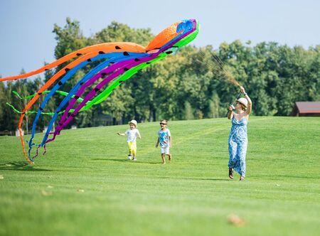 convivencia familiar: La familia feliz volar cometa juntos en un campo verde