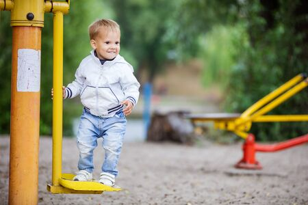 outdoor exercise: Happy toddler boy playing in outdoor fitness park