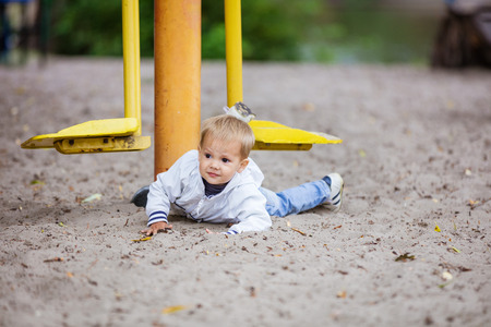 hurt: Toddler boy falling from outdoor exercise machine Stock Photo