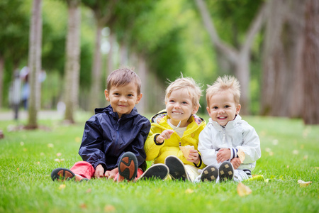 young boys: Three young boys sitting on the grass in a park and smiling, the boy in the middle eating ice cream
