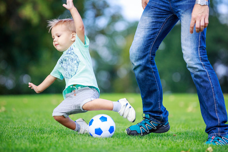 toddler boy: Young man and toddler son playing football in park