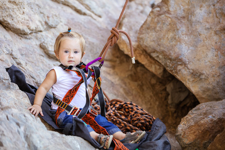fastened: Little girl fastened to rock climbing gear and sitting on cliff