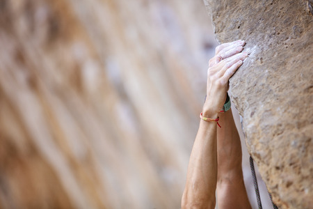 Close up climbers hands on a cliff