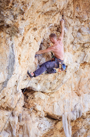 full height: Male rock climber on a face of a cliff Stock Photo