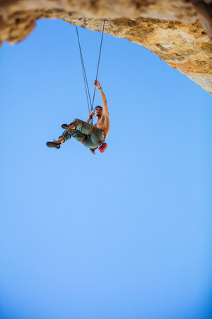 rappel: Male rock climber hanging on rope