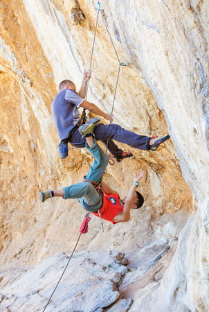 heavy risk: Two male climbers hanging on a rope. After a heavier leader fell off the cliff a lighter belayer (in a red vest) was pulled into the air.