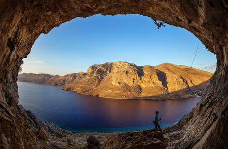 Male rock climber climbing along roof in cave before sunset. Kalymnos Island, Greece. photo