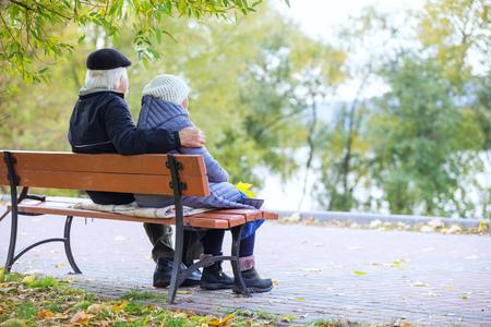 秋の公園でベンチに座っている年配のカップル 写真素材