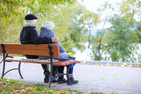 Senior couple sitting on bench in autumn park