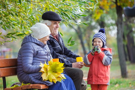 great grandmother: Senior couple and grandson drinking hot tea in autumn park Stock Photo