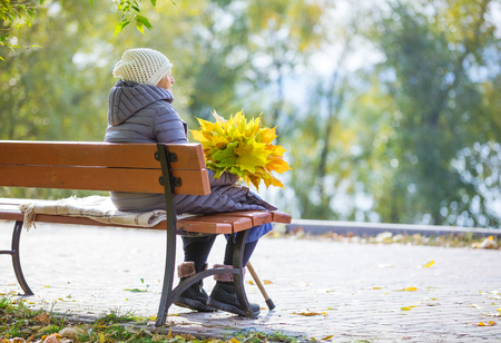 Senior woman sitting on bench in park and holding bunch of autumn leaves