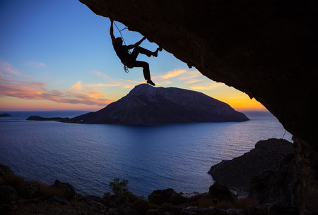 success man: Young man climbing along roof in cave at sunset