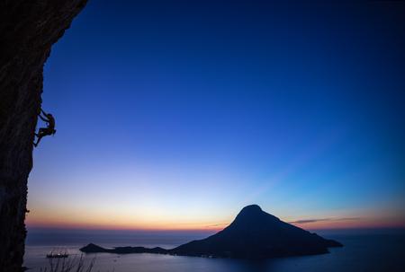 overhanging: Rock climber on overhanging cliff at sunset. Kalymnos Island, Greece.