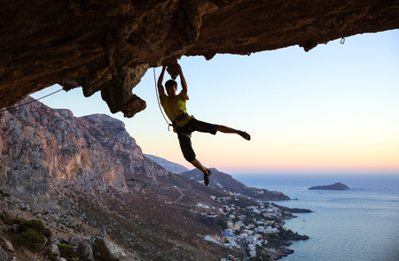 overhanging: Rock climber jumping on handholds while climbing overhanging cliff