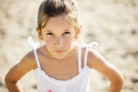suspiciously: Young girl looking suspiciously while standing on beach