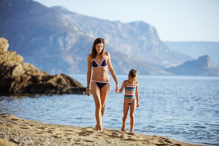mignonne petite fille: Jeune femme et sa fille marchant le long de la plage de sable Banque d'images