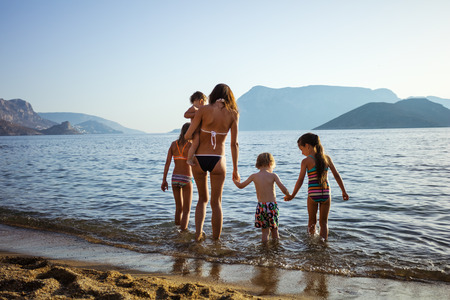 view girl: Young woman with four children walking in shallow sea waters