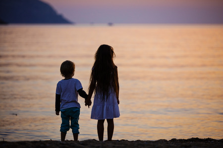 children holding hands: Young boy and girl holding hands while standing on beach at sunset