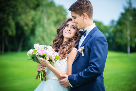 young male: Beautiful young bride and groom going to kiss outdoors Stock Photo