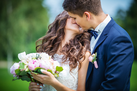 summer dress: Beautiful young bride and groom kissing in park