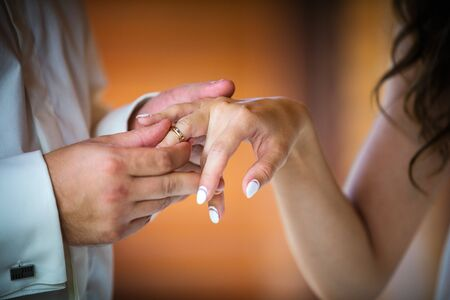 Groom putting ring on brides finger, cropped view indoors