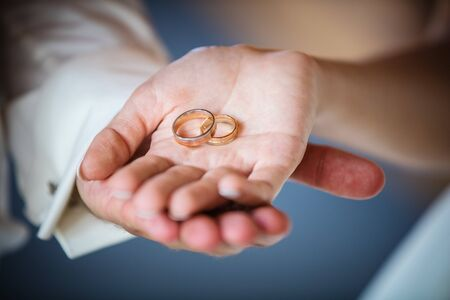 cropped: Newlyweds holding golden rings, cropped view Stock Photo