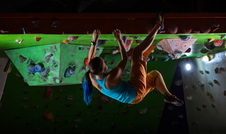 extreme sports: Young woman bouldering along ceiling of indoor climbing gym Stock Photo