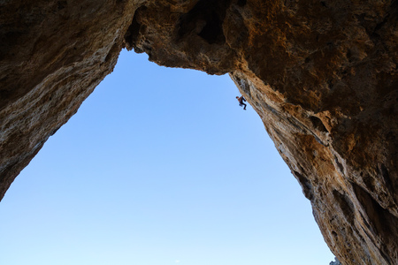 lead rope: Silhouette of a rock climber hanging on rope while climbing in cave, Telendos Island, Greece Stock Photo