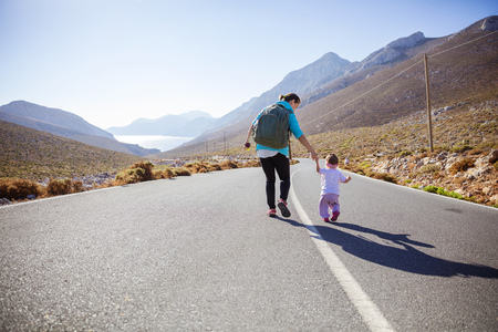 Young woman and little daughter walking down road in mountainous