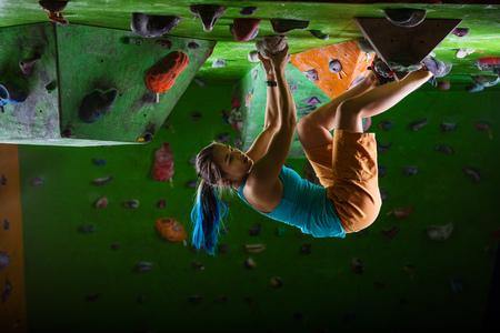bouldering: Woman bouldering on climbing gym