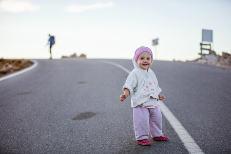 Cute little girl standing on road, her father waiting in distance Stock Photo