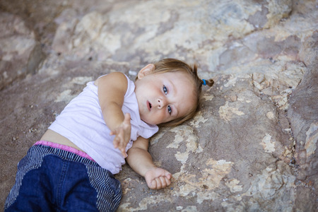 babies hands: Little girl lying on rock and stretching out hand. Playful mood or asking for help concept. Stock Photo