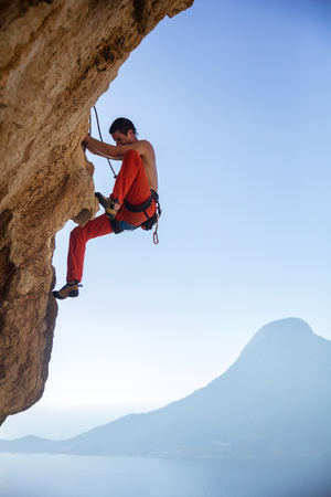 lead rope: Young man climbing on overhanging cliff against blue sky, Kalymnos Island, Greece