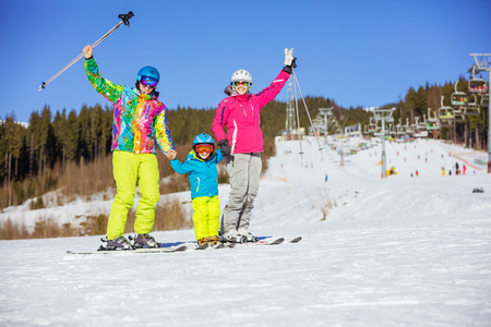 kids at the ski lift: Cheerful family of three standing on ski slope, parents lifting hands with ski poles