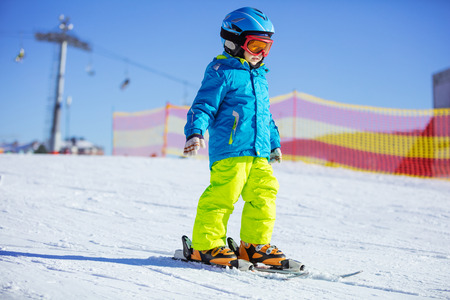 kids at the ski lift: Little boy skiing downhill, wearing safety helmet and goggles Stock Photo