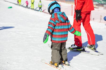 Jonge skiër en ski-instructeur die omhoog helling in beginners gebied