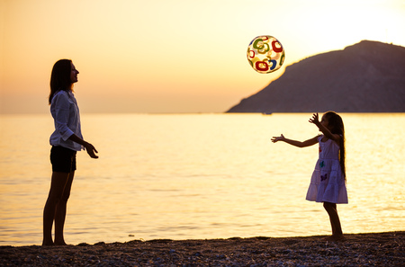 Mother and daughter playing ball on beach at sunset Stock Photo