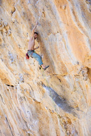 overhanging: Male rock climber on challenging route on overhanging cliff