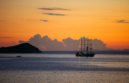 View of cruise sailing ship and small ferry boat by rocky coast at sunset