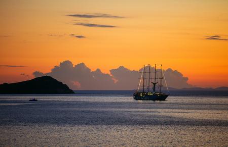 Vue de bateau à voile de croisière et petit ferry par côte rocheuse au coucher du soleil
